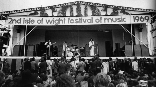 August 1969, the 2nd Annual Isle of Wight festival, which featured The Who's 2,500-watt WEM PA system. Visible are three Marshall 8x10 PA cabinets per stage side, and WEM columns and cabs set up in the backline as foldback.